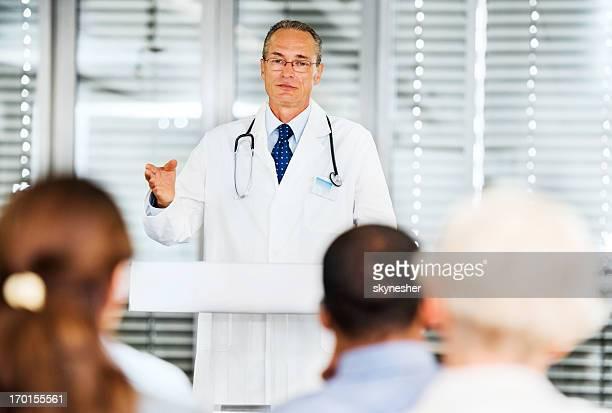 Mature male doctor giving a speech on seminar.