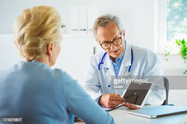 médico masculino maduro que muestra los resultados de las pruebas médicas en la tableta digital - izusek fotografías e imágenes de stock