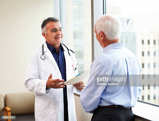 A mature male doctor speaking to a senior male pat