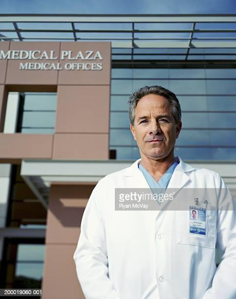 Mature homme médecin debout à l'extérieur, portrait de medical de