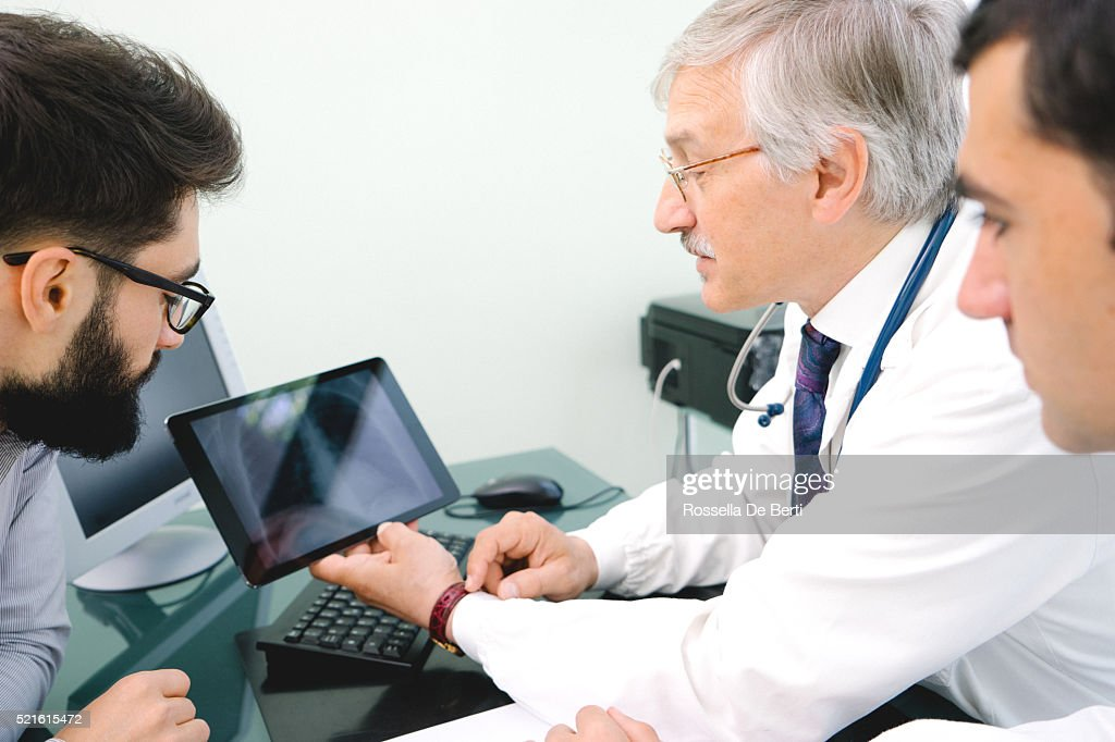 Mature Male Doctor Using A Digital Tablet For His Diagnosis. : Stock Photo