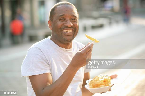 mature male eating fish and chips - english lake district stock pictures, royalty-free photos & images