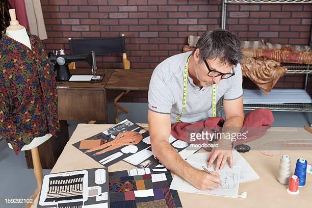 Mature male fashion designer working on sketch in design studio