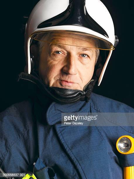 Mature male firefighter wearing helmet, portrait
