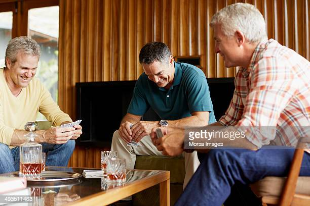 Mature male friends playing cards