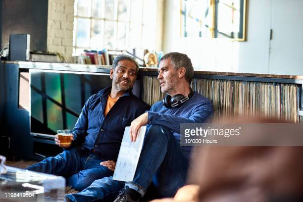 mature male friends sitting together listening to records - close to stock pictures, royalty-free photos & images