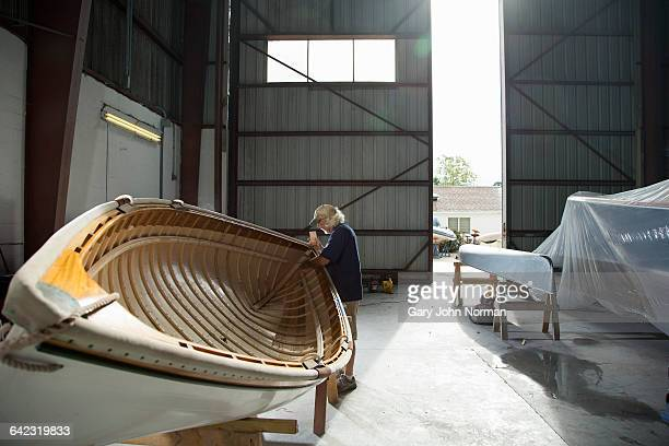 Mature male handcrafting wooden boat