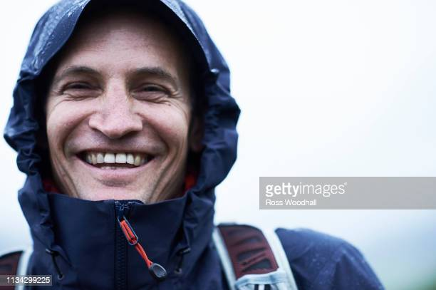 mature male hiker in hooded anorak in rain, portrait, manigod, rhone-alpes, france - rhone alpes stock photos and pictures