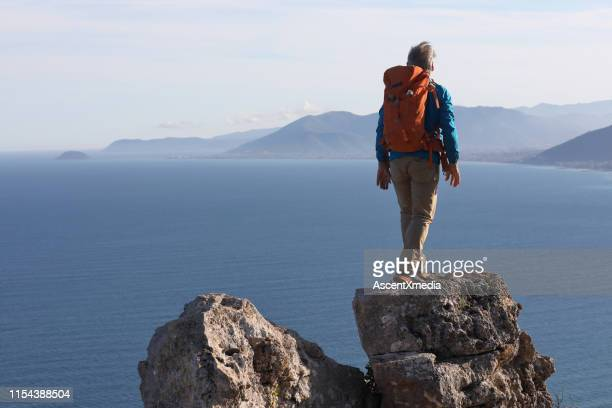 mature male hiker on a rock summit above the sea - early retirement stock pictures, royalty-free photos & images