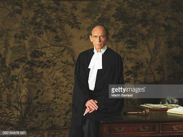 mature male judge perched on edge of desk, portrait - ceremonial robe stock pictures, royalty-free photos & images