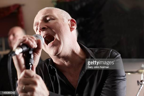 mature male lead singer singing into microphone - lead singer stock pictures, royalty-free photos & images