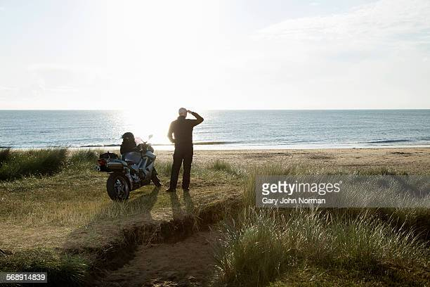 Mature male motorcyclist enjoys view after a ride.