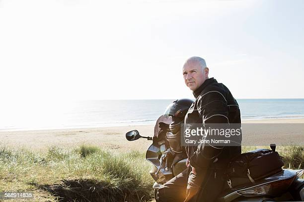 Mature male motorcyclist leaning on his bike.