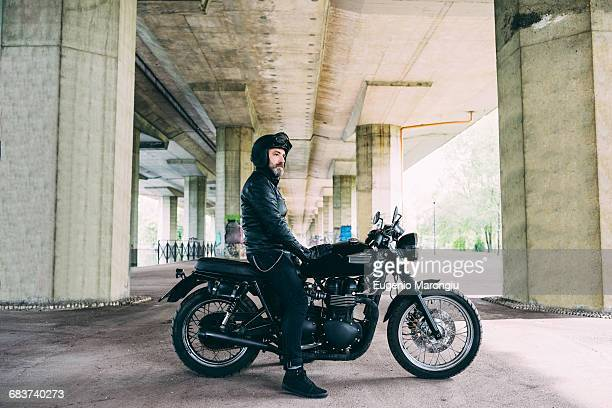 mature male motorcyclist sitting on motorcycle looking out from under flyover - crash helmet stock pictures, royalty-free photos & images