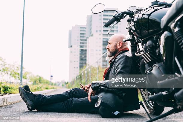 Mature male motorcyclist sitting on roadside leaning on motorcycle with smartphone