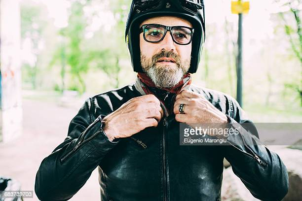Mature male motorcyclist wearing eyeglasses fastening leather jacket