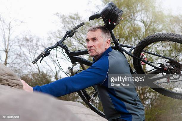 Mature male mountain biker carrying bike over rock formation