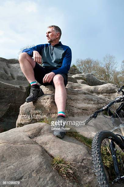 Mature male mountain sitting and looking out from rock formation