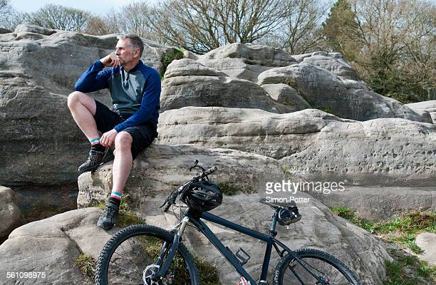 Mature male mountain sitting on rock formation