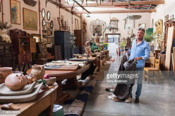 mature male owner of antique store in his shop - finanzwirtschaft und industrie stock-fotos und bilder