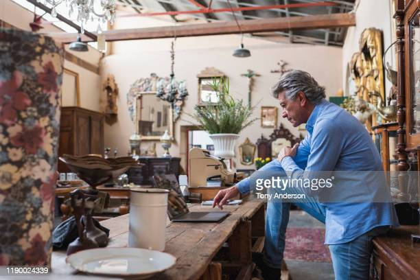 mature male owner of antique store using laptop in his shop - disruptaging stock pictures, royalty-free photos & images