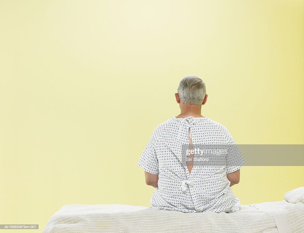 Mature male patient sitting on gurney in hospital gown, rear view : Stock Photo