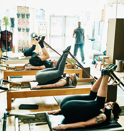 Mature male pilates instructor leading class on pilates reformers in fitness studio - gettyimageskorea