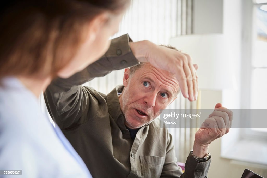 Mature male professional explaining to female colleague at board room : Stock Photo