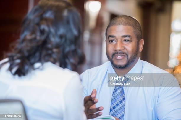 成熟した男性の専門家は、クライアントとの会議で好奇心旺盛に見えます - リクルーター ストックフォトと画像