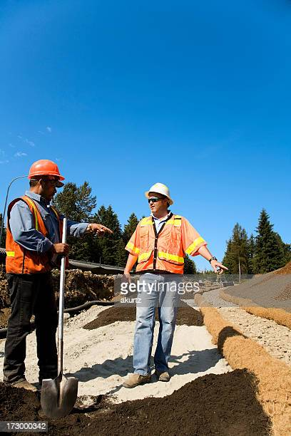 Mature male Project Manager overseeing Erosion control safety gear orange