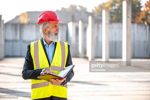 mature male project manager visiting construction site - waistcoat stock pictures, royalty-free photos & images