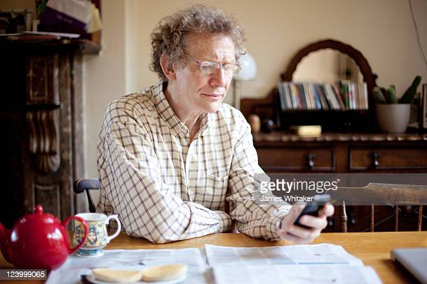 Mature male reads phone at breakfast table