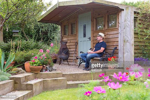 mature male relaxing in his garden - shed stock pictures, royalty-free photos & images