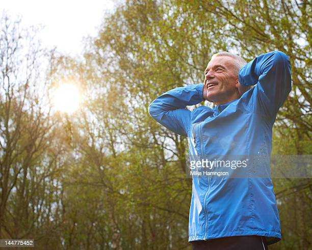 Mature Male Runner Stretching Arms In Park