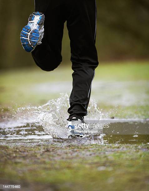 mature male running through puddle - human foot stock pictures, royalty-free photos & images