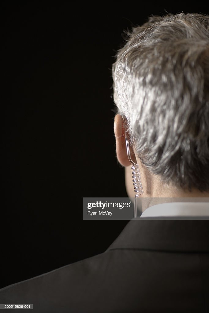Mature male secret service agent wearing hands-free device, rear view :  Stock Photo