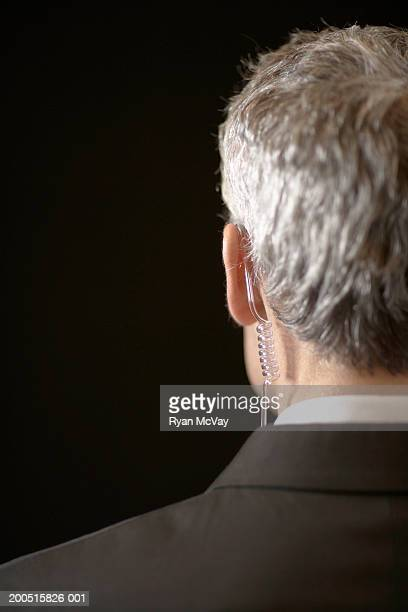 Mature male secret service agent wearing hands-free device, rear view