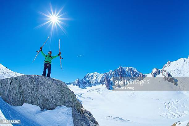 Mature male skier holding up skis on Mont Blanc massif, Graian Alps, France