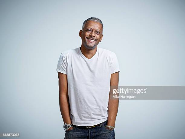 mature male smiling with hands in pockets - maglietta foto e immagini stock