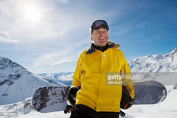 mature male snowboarder with snowboard on mountain, portrait