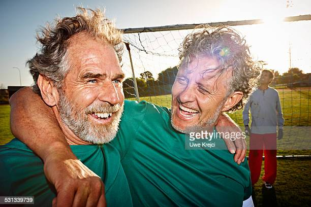 Mature male soccer players celebrating, portrait