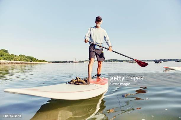 Mature male standup paddle boarder has fun in Casco Bay, Maine