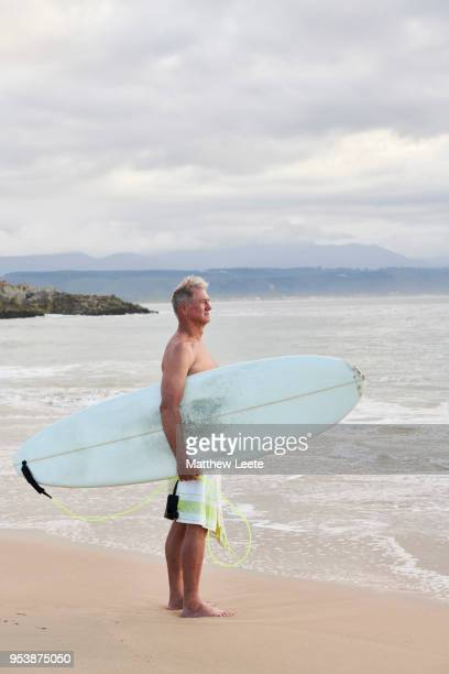 mature male surfer at beach - matthew hale stock pictures, royalty-free photos & images