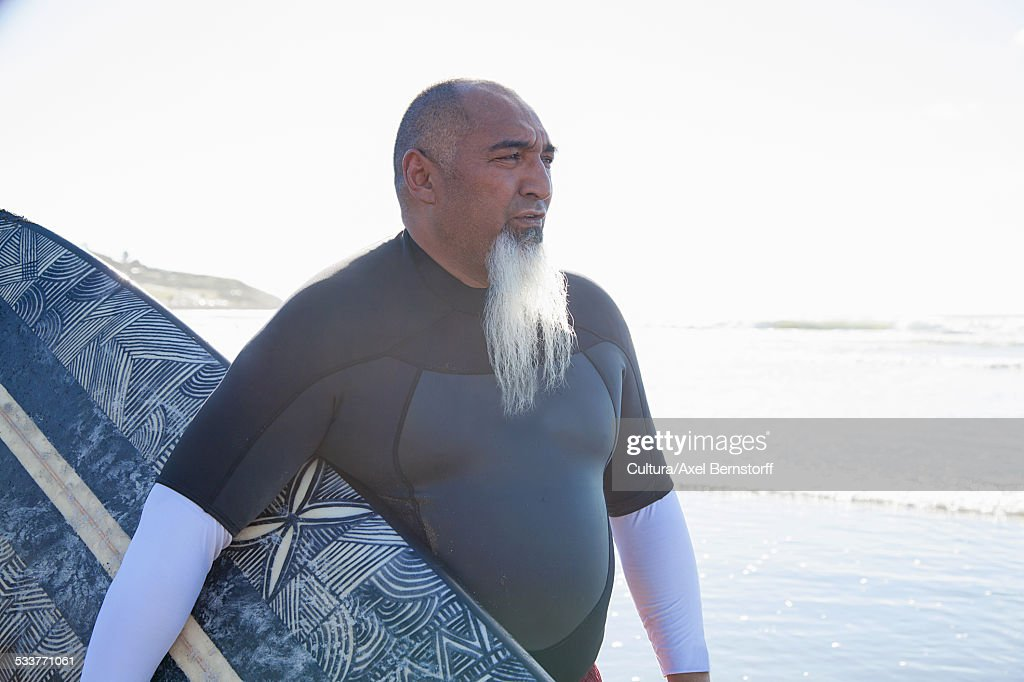 Mature male surfer strolling on beach with surfboard : Foto stock