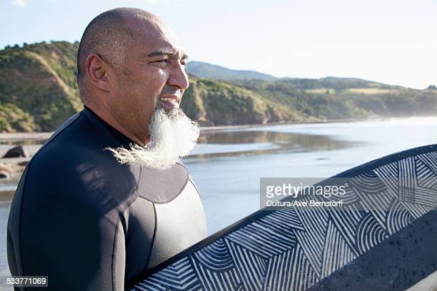 Mature male surfer with surfboard watching sea