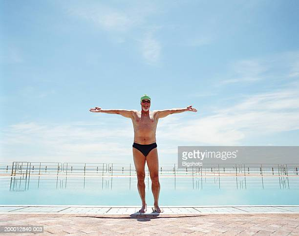 mature male swimmer, arms outstretched, portrait - old man in speedo stock photos and pictures