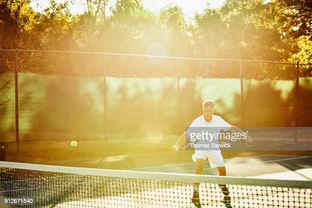 Mature male tennis player hitting backhand return at net during early morning tennis match