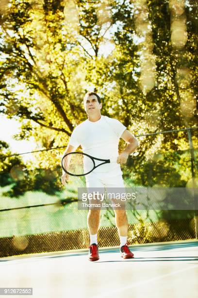 Mature male tennis player playing early morning match