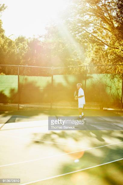 Mature male tennis player preparing to serve during early morning tennis match