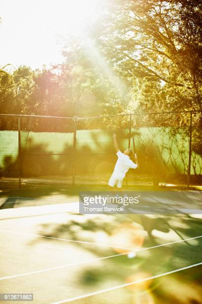Mature male tennis player serving during early morning match